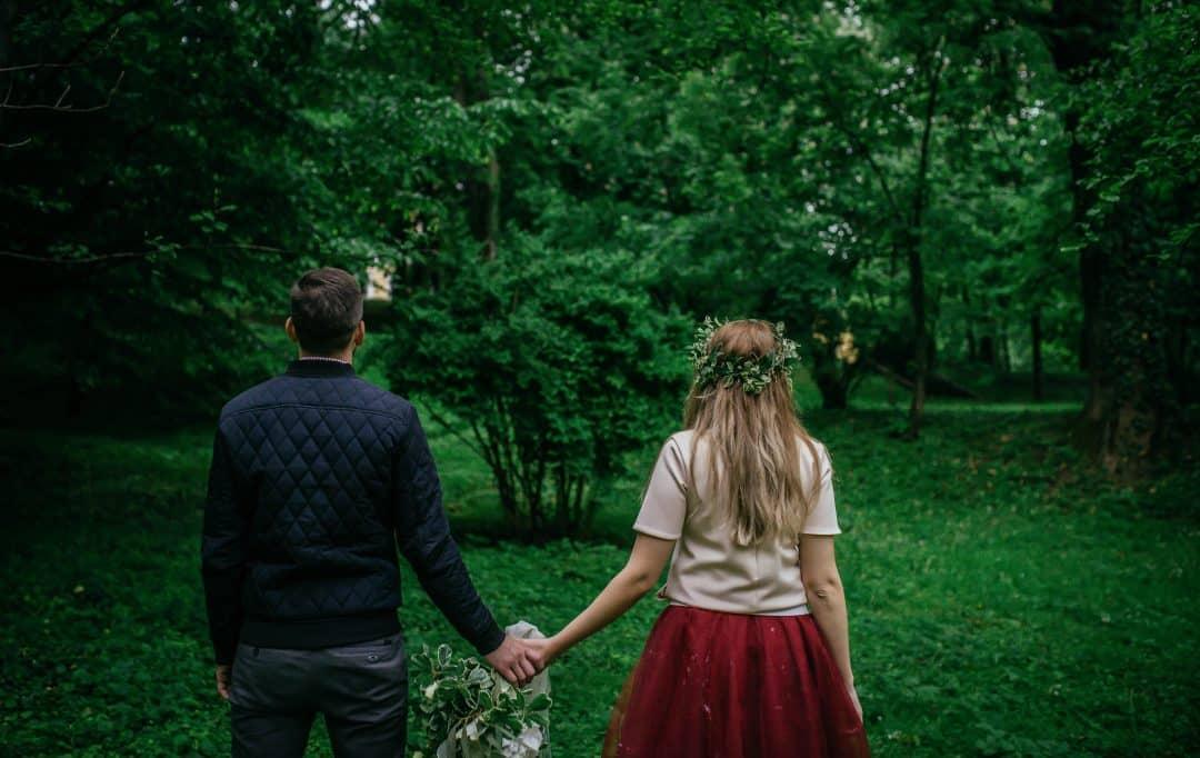 Hombre y mujer de espaldas tomados de la mano