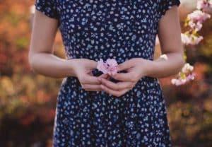 Mujer sosteniendo flores pequeñas