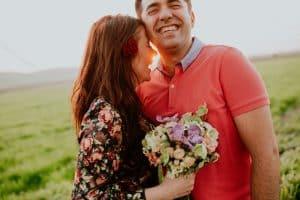 Hombre y mujer conn ramo de flores sonriendo