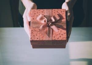 Manos femeninas sosteniendo una caja de regalo
