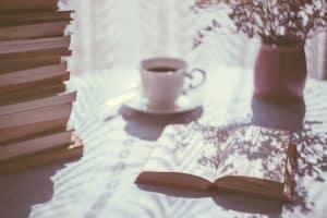 Taza de café, libros, flores, sol.