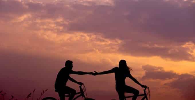 Hombre y mujer montando bicilceta tomados de la mano